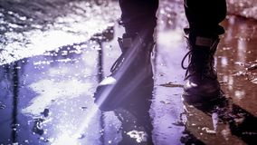 在站立在水坑的时兴的起动的人的腿 图库摄影