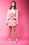 在站立在演播室的桃红色外套的年轻亚洲女性时装模特儿 免版税图库摄影