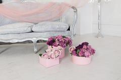 在站立在灰色沙发附近的一个桃红色圆的箱子的桃红色和紫色玫瑰 库存图片