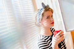 在站立在白色的典雅的美丽的白肤金发的画报少妇饮用的咖啡的特写镜头蒙蔽太阳被点燃的窗口背景 免版税库存图片