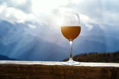 在站立在美好的山背景前面的一张木桌上的野餐的红葡萄酒玻璃 免版税库存图片