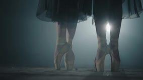 在站立在聚光灯的姿势的pointe的女性脚在黑背景 两个女孩在他们的脚趾同时站立 影视素材
