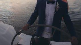 在站立在风船的一个方向盘后的衣服的商人 驾驶在日落的年轻水手游艇 股票录像