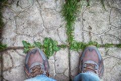 在站立在鹅卵石瓦片的运动鞋的脚 免版税库存照片