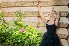 在站立在wal附近的黑礼服的性感的美好的白肤金发的夫人模型 库存图片