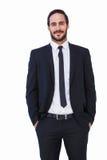 在站立用在口袋的手的衣服的微笑的商人 库存照片