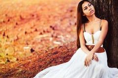 在童话森林里塑造美丽的白色礼服的华美的少妇坐地面 免版税库存照片