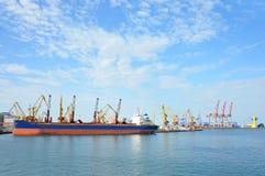 在端口起重机之下的散货船 免版税库存图片