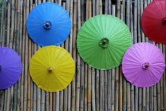 在竹墙壁上的五颜六色的伞装饰 免版税库存照片