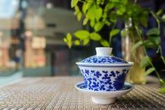 在竹子被编织的席子,中国的蓝白陶瓷茶杯 库存图片