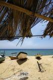 在竹小屋,在离开的沙滩搁浅的传统渔夫小船下的美好的风景 免版税库存照片