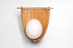 在竹帆布篮的白鸡蛋在白色 免版税图库摄影