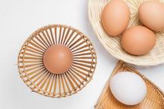 在竹帆布篮的鸡蛋在白色 库存图片