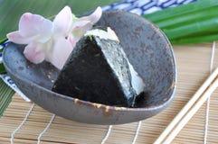 在竹席子上把放的Onigiri日本盘 库存图片