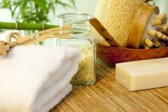 在竹席子温泉概念的腌制槽用食盐和毛巾 免版税库存照片