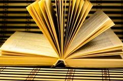 在竹席子的一本开放书 免版税库存图片