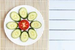 在竹席子的五颜六色的被切的新鲜的有机菜 成熟蕃茄和黄瓜以花的形式 在木桌上的顶视图与 免版税库存照片