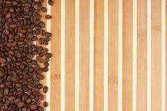 在竹席子的咖啡豆 免版税库存照片