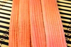 在竹席子的武术橙色传送带 库存图片