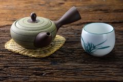 在竹席子的热的茶罐有在木桌上的杯子的 免版税库存照片