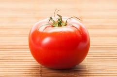 在竹桌上的完善的红色蕃茄 免版税库存照片
