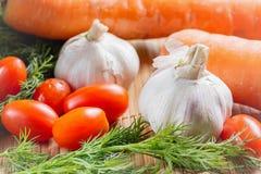 在竹桌布的菜 新鲜的西红柿,大蒜,红萝卜,莳萝接近  免版税库存图片