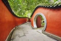在竹森林围拢的红色墙壁段落的圆的门 免版税图库摄影