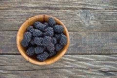 在竹碗的黑莓果子在木背景 库存图片