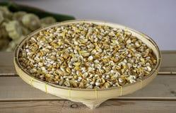 在竹篮子的种子玉米在木桌上 免版税库存图片