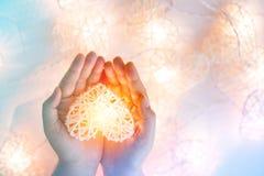 在竹篮子的软的淡色橙色灯在心脏形状在两手 图库摄影