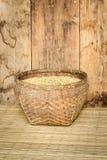 在竹篮子的水稻在垫席纺织法和木头上backgrou 免版税库存照片