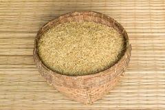 在竹篮子的水稻在垫席纺织法背景 库存图片