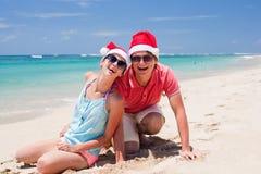 在笑在热带的圣诞老人帽子的新夫妇 免版税库存图片