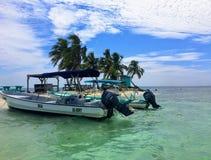 在笑的鸟Caye热带海岛的shallows停住的两条小船  免版税库存照片