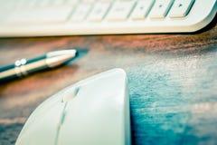 在笔前面的白色计算机老鼠和在木表上的一个白色键盘 库存图片