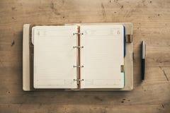 在笔木背景旁边打开空的螺旋坚硬盖子笔记本 图库摄影