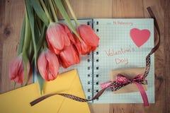 在笔记本、新鲜的郁金香、情书、礼物和心脏写的情人节,华伦泰的装饰 库存图片