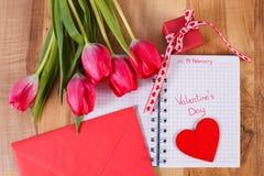 在笔记本、新鲜的郁金香、情书、礼物和心脏写的情人节,华伦泰的装饰 免版税库存照片