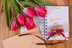 在笔记本、新鲜的郁金香、情书和礼物写的情人节,华伦泰的装饰 免版税库存图片