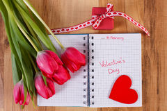 在笔记本、新鲜的郁金香、被包裹的礼物和心脏写的情人节,华伦泰的装饰 库存照片