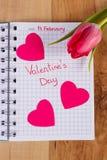 在笔记本、新鲜的郁金香和心脏写的情人节,华伦泰的装饰 库存图片