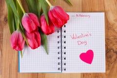 在笔记本、新鲜的郁金香和心脏写的情人节,华伦泰的装饰 免版税库存照片