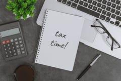 在笔记本写的税时间 有膝上型计算机、笔、笔记本和计算器的工作书桌 库存图片