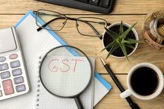 在笔记本在放大镜和计算器下,笔和咖啡的GST词在棕色木背景 在视图之上 库存图片