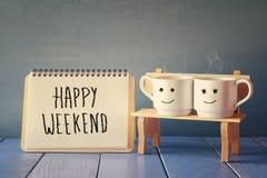 在笔记本旁边的咖啡杯与词组愉快的周末 免版税库存图片