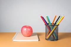 在笔记本的一个苹果和A堆颜色书写 免版税图库摄影