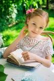 在笔记本的一点微笑的女孩文字室外在公园 vi 免版税图库摄影