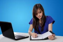 在笔记本的亚洲学生女孩文字,在蓝色背景 库存照片