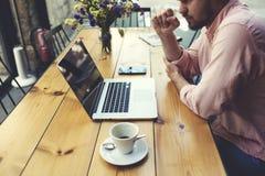 在笔记本的周道的商人工作,当坐在现代咖啡店内部时的木桌上 库存图片