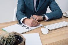 在笔记本的商人文字,当坐在办公室桌上时 免版税库存照片